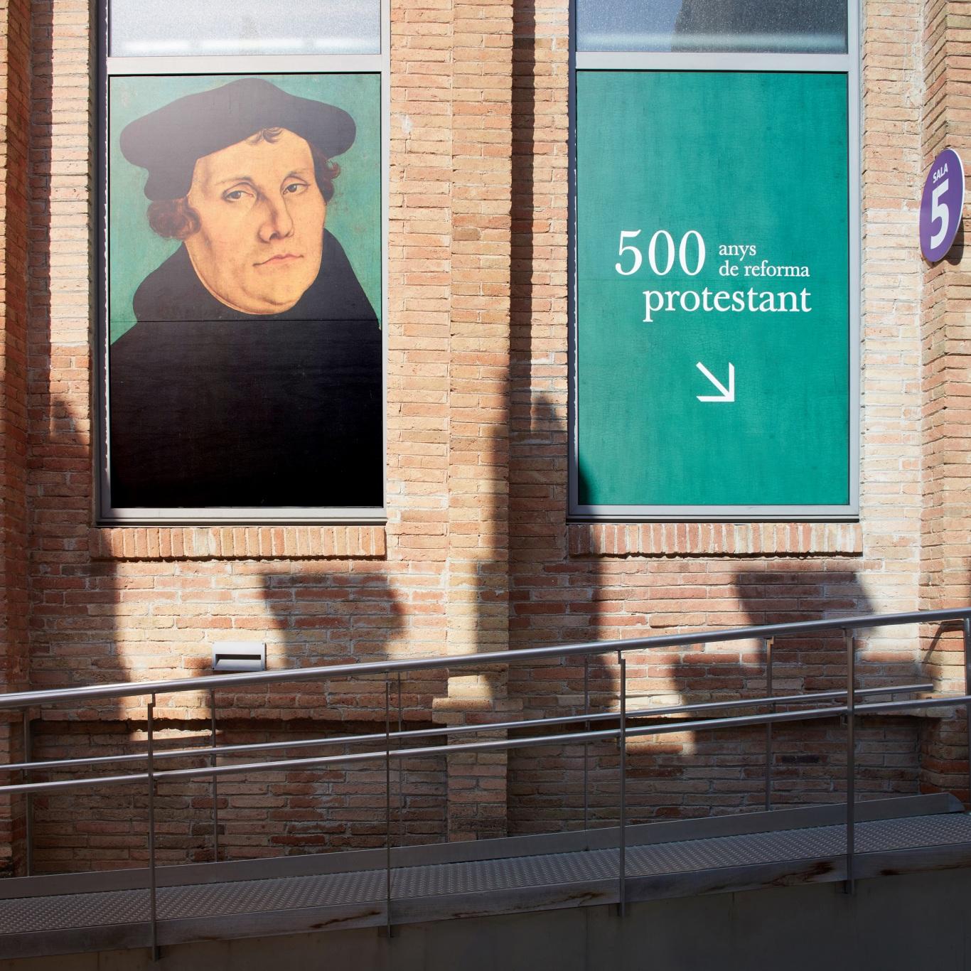 Exposición protestantes Caixaforum. Fachada Caixaforum. Carteles de la exposición con la imagen de Martín Lutero.