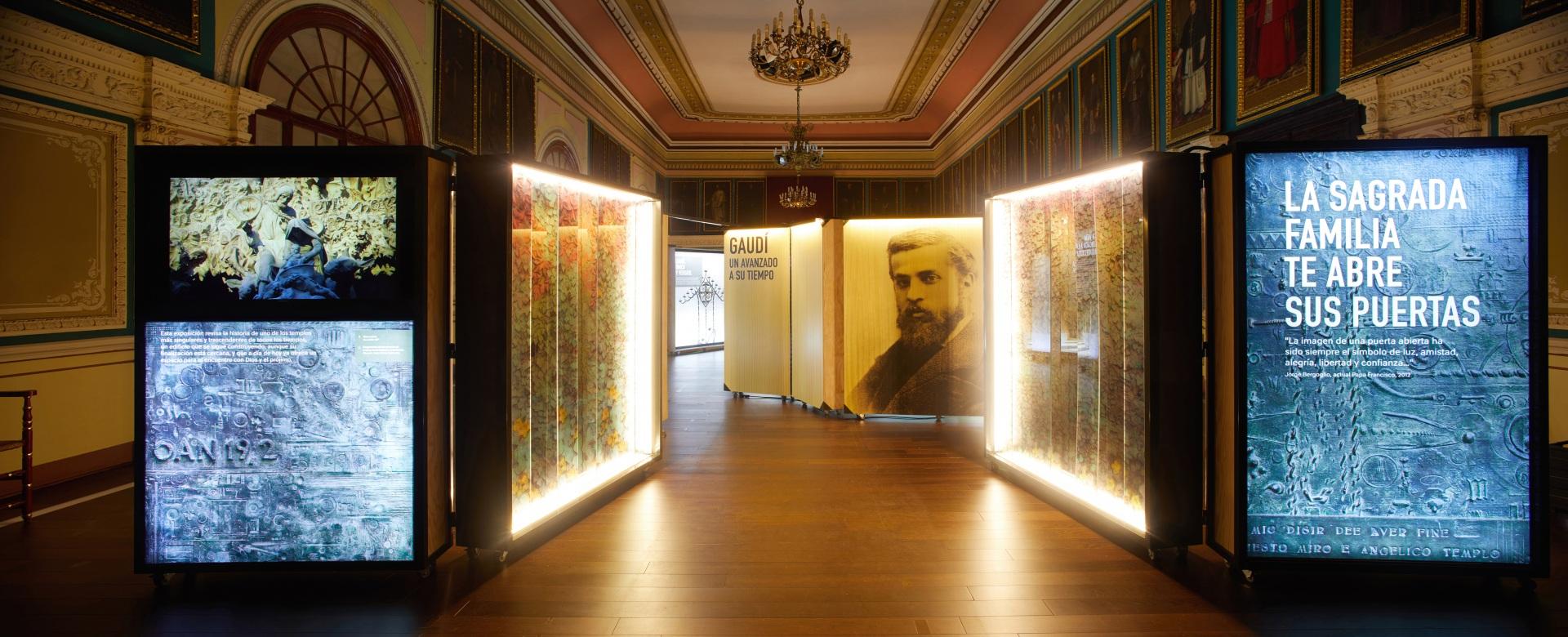 Exposición Gaudí Sagrada Familia. Entrada, puertas, imagen de Gaudí, cajas iluminadas.
