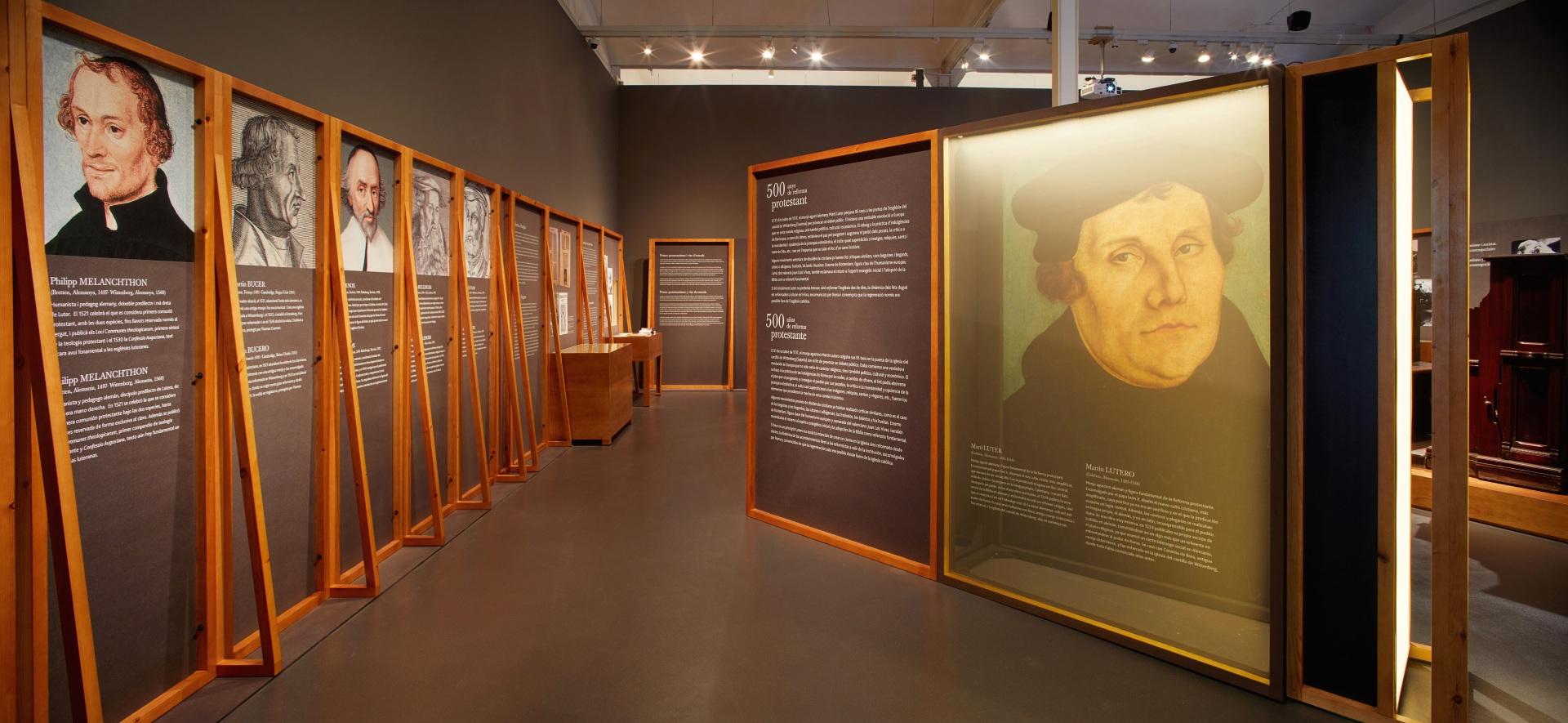 Exposición protestantes Caixaforum. Caja iluminada con retrato de Martín Lutero y paneles con retratos de otros líderes del protestantismo.