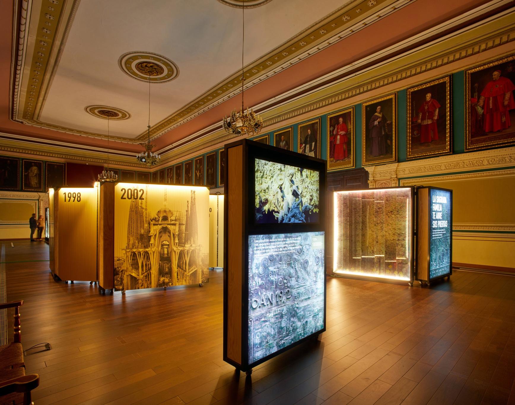 Exposición Gaudí Sagrada Familia. Cajas iluminadas, puertas de entrada, edificio en construcción. Sala antigua con retratos de cardenales.