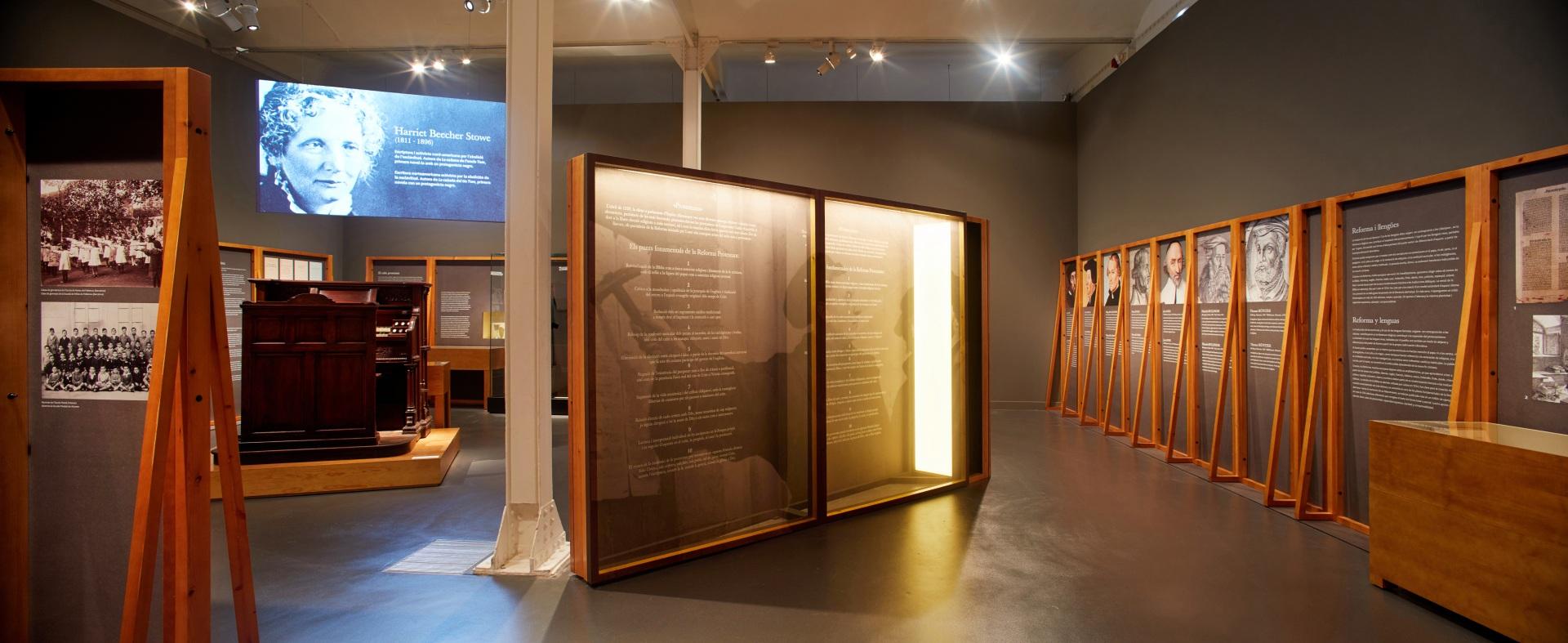 Exposición protestantes Caixaforum. Vitrinas y paneles de madera, proyección audiovisual y armónium.