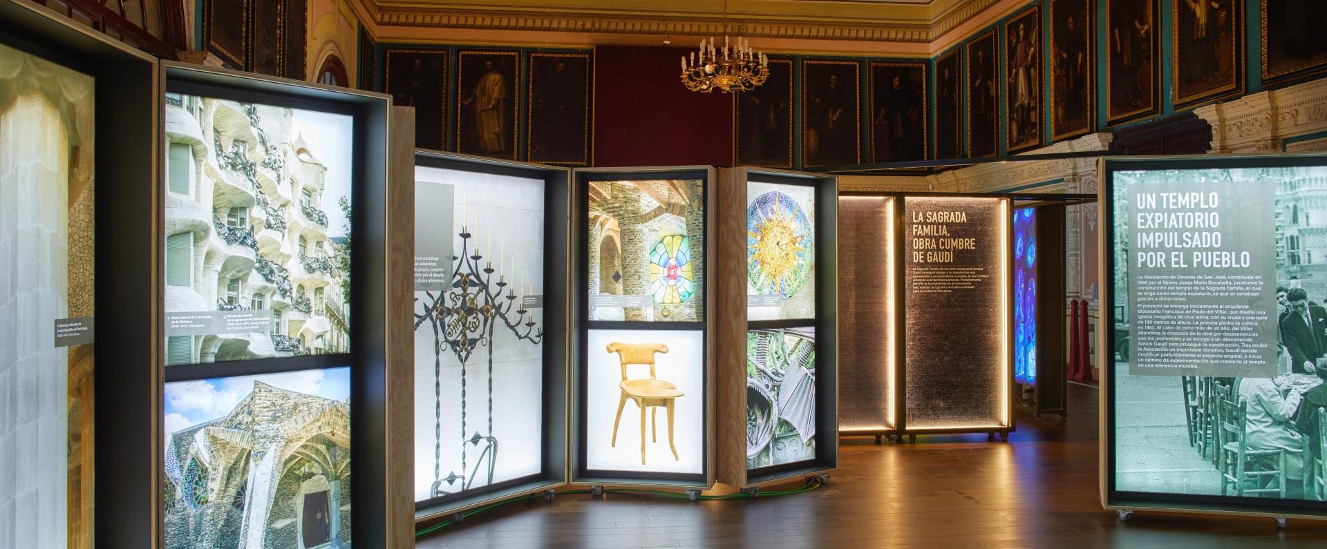 Exposición Gaudí Sagrada Familia. Imágenes de edificios y muebles en cajas iluminadas. Retratos de cardenales en sala antigua.