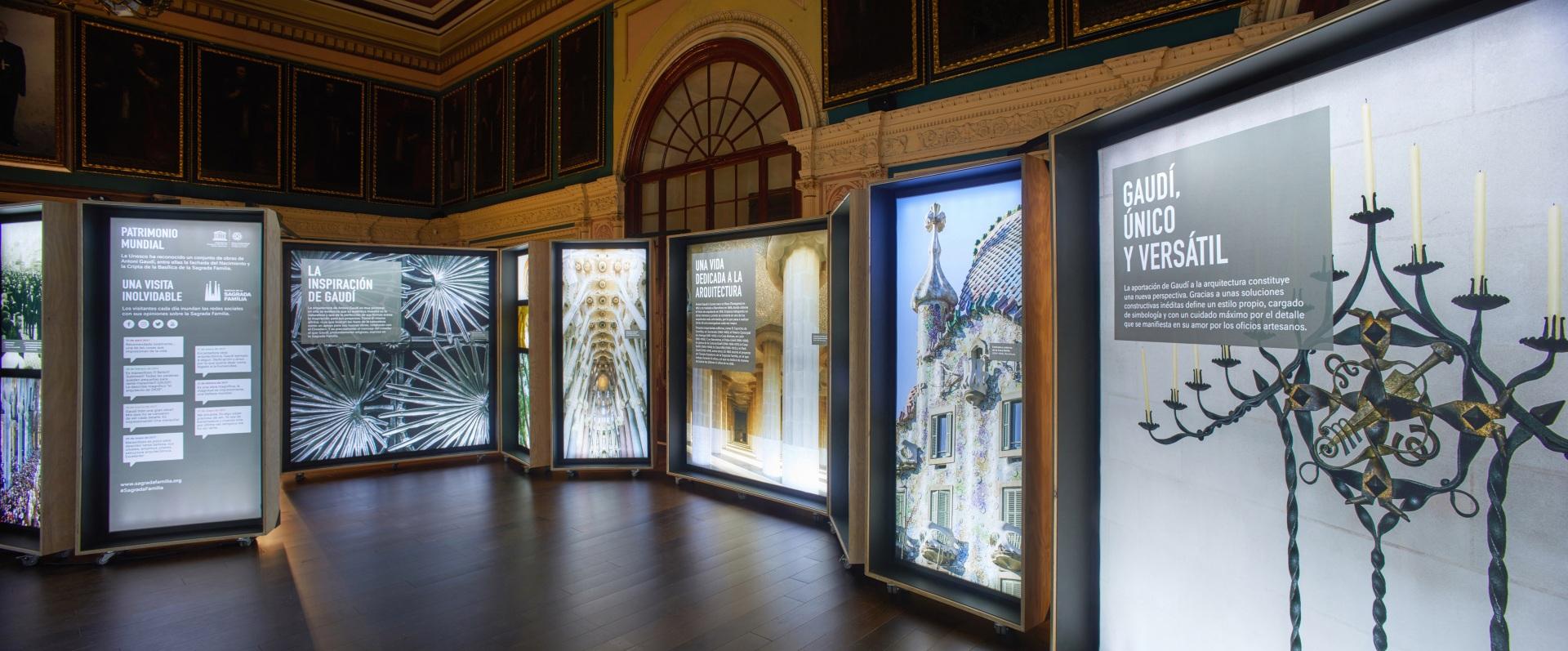 Exposición Gaudí Sagrada Familia. Imágenes de candelabros, edificios y detalles arquitectónicos en cajas iluminadas.
