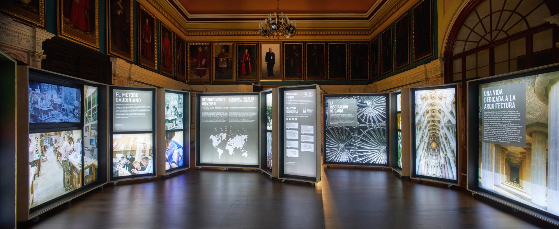 Exposición Gaudí Sagrada Familia. Imágenes de la arquitectura de Gaudí en cajas iluminadas. Sala antigua con retratos de cardenales.