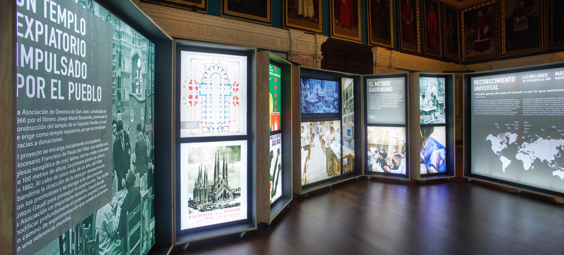 Exposición Gaudí Sagrada Familia. Plano de edificio y otras imágenes en cajas iluminadas.