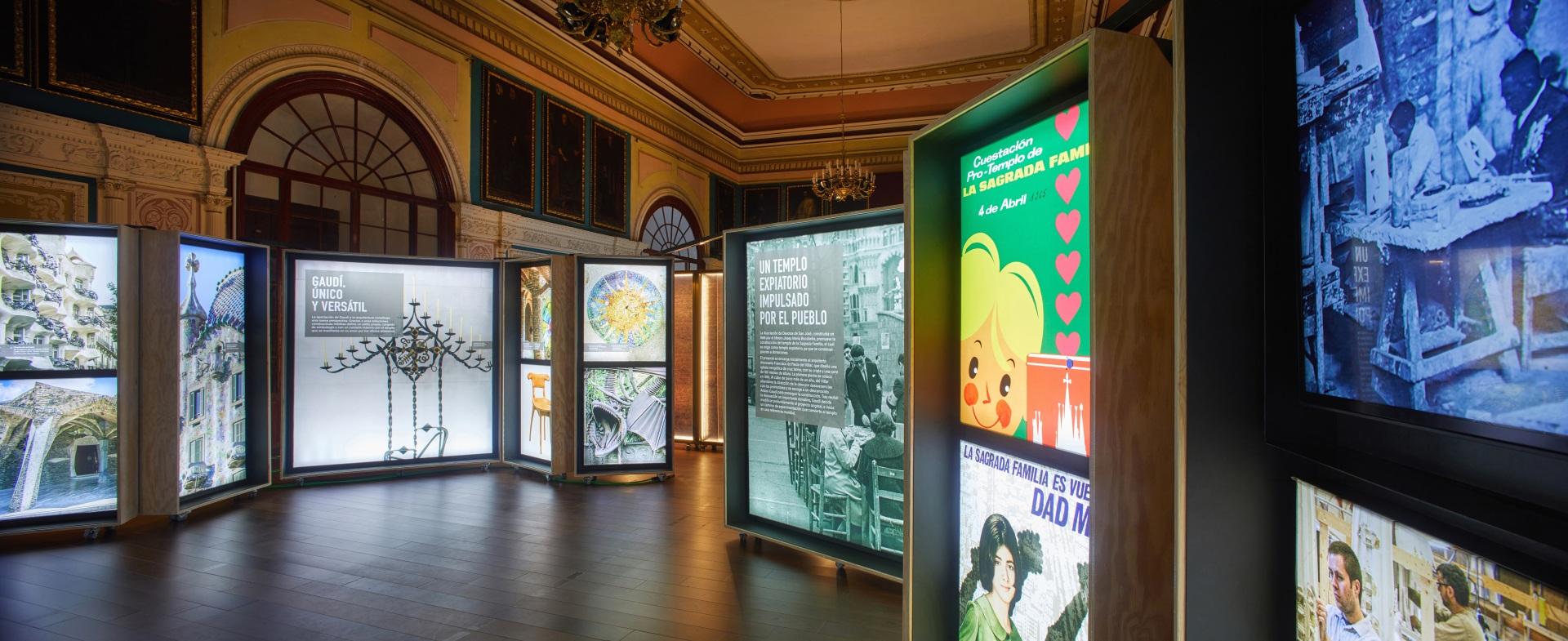 Exposición Gaudí Sagrada Familia. Imágenes de candelabro, edificios y carteles en cajas iluminadas.