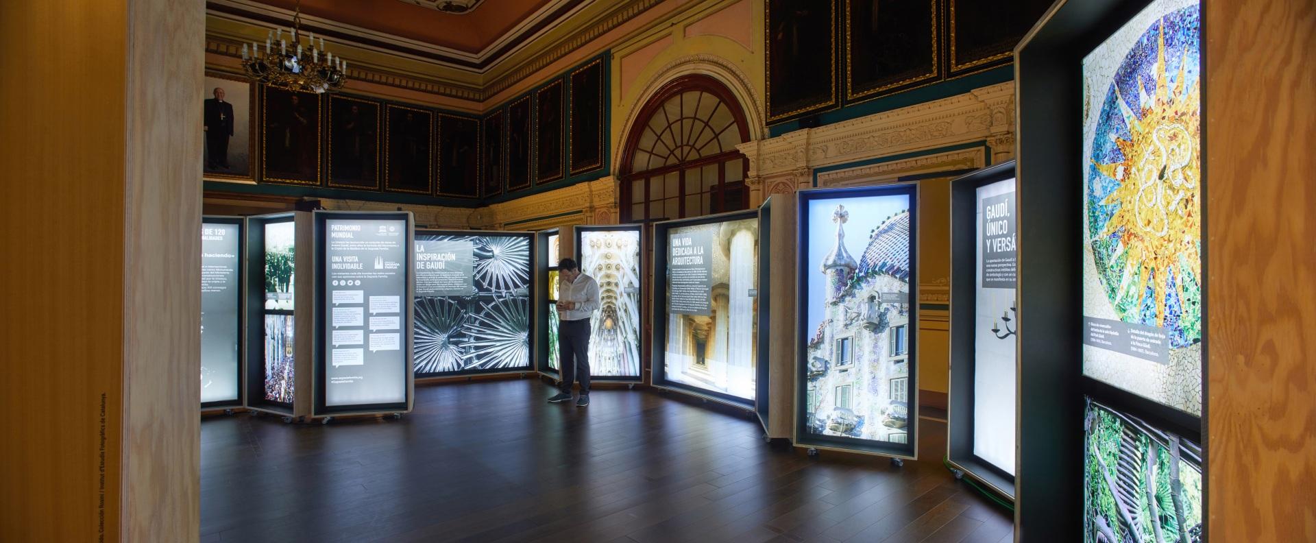 Exposición Gaudí Sagrada Familia. Imágenes de edificios y detalles arquitectónicos en cajas iluminadas.