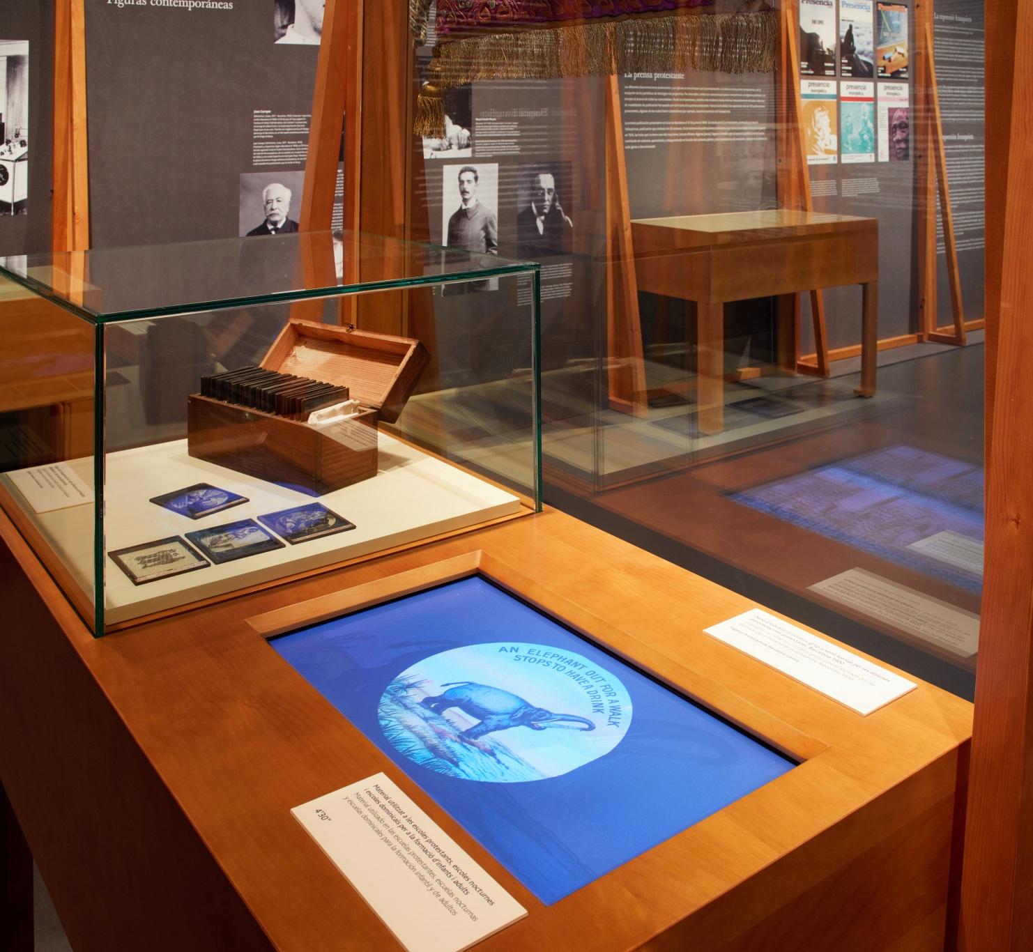 Exposición protestantes Caixaforum. Vitrinas y paneles de madera, proyección audiovisual y armónium. Vitrina con diapositivas y audiovisual integrado. De fondo, paneles y vitrinas.