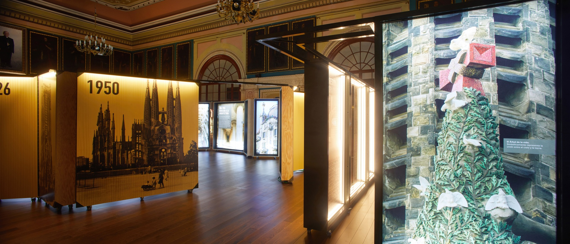 Exposición Gaudí Sagrada Familia. Imágenes del edificio en cajas iluminadas y madera. En sala antigua.