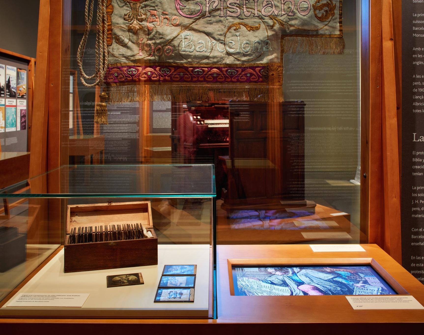 Exposición protestantes Caixaforum. Vitrinas y paneles de madera, proyección audiovisual y armónium. Vitrina con diapositivas y estandarte, audiovisual integrado. De fondo, armónium.