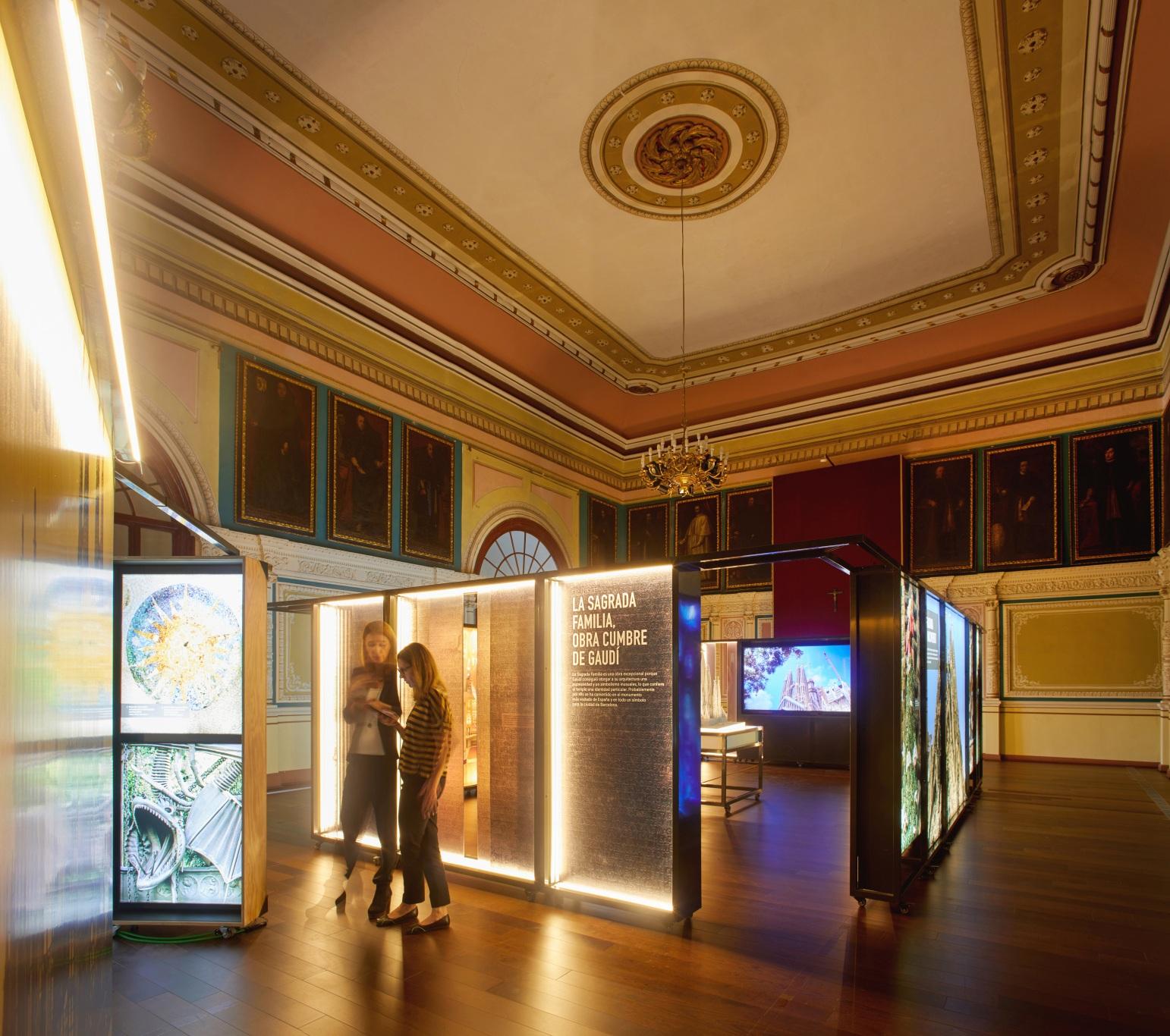 Exposición Gaudí Sagrada Familia. Imágenes en cajas iluminadas. Dos visitantes en sala antigua.