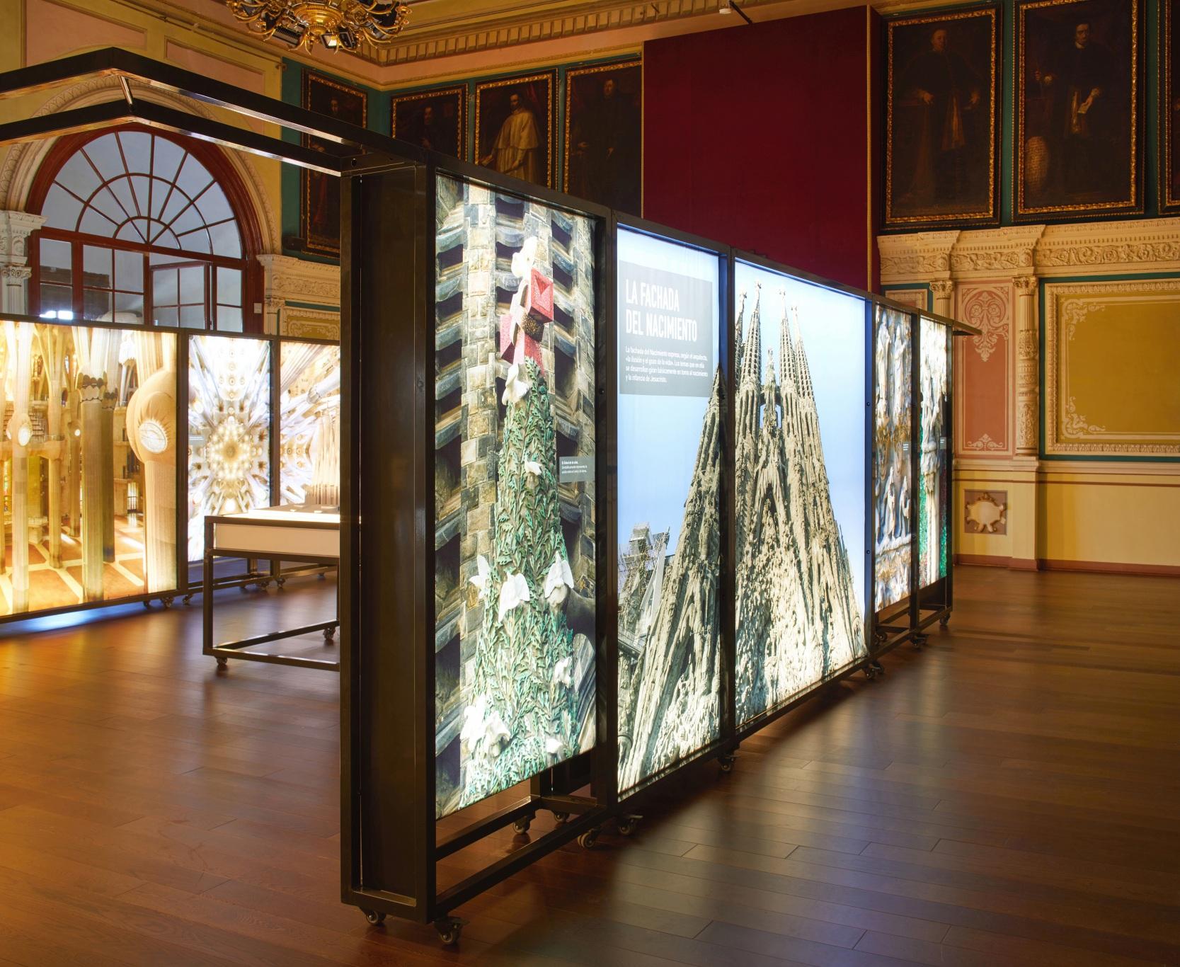 Exposición Gaudí Sagrada Familia. Imágenes del edificio en cajas iluminadas. En sala antigua.