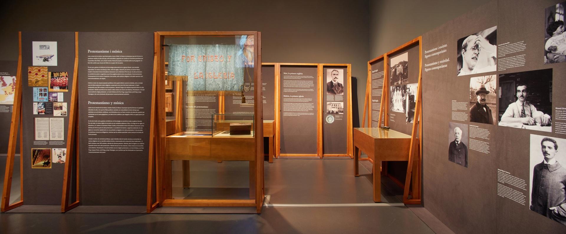 Exposición protestantes Caixaforum. Paneles y vitrinas con estandarte y retratos de personajes protestantes relevantes.