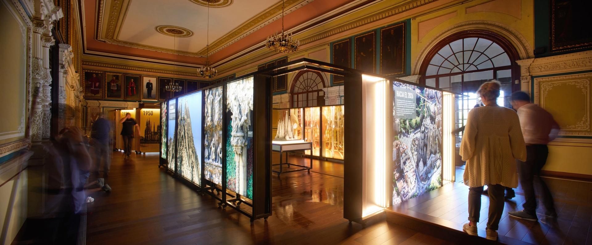Exposición Gaudí Sagrada Familia. Imágenes del edificio en cajas iluminadas, maqueta. Visitantes de la exposición en sala antigua con retratos de cardenales.