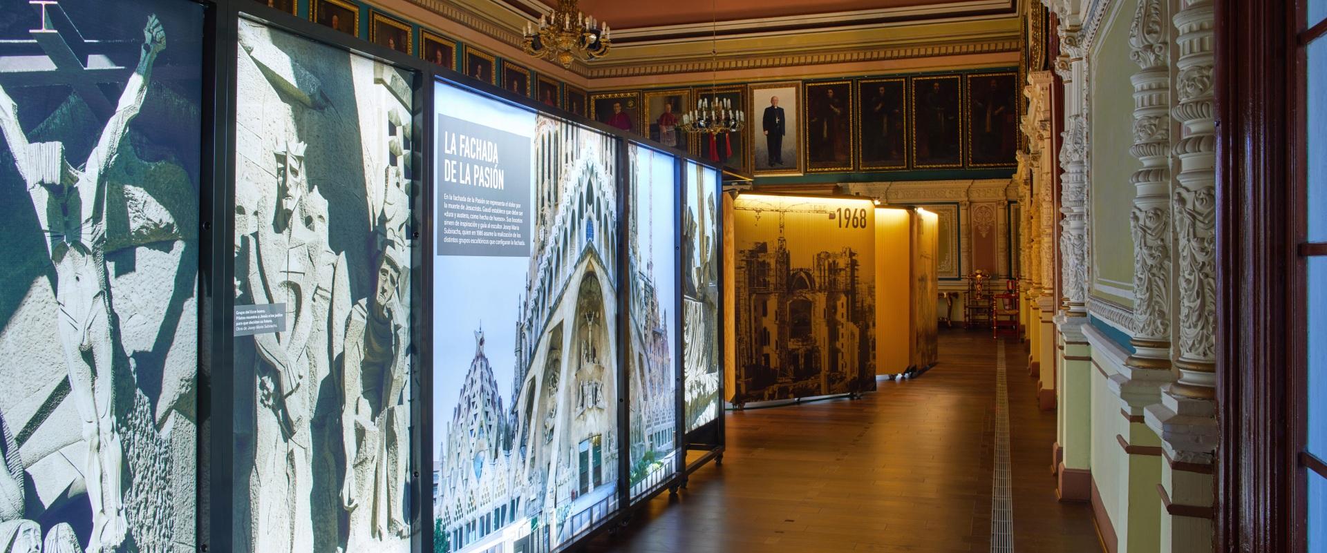 Exposición Gaudí Sagrada Familia. Imágenes del edificio en cajas iluminadas. En sala antigua con retratos de cardenales y columnas decoradas.