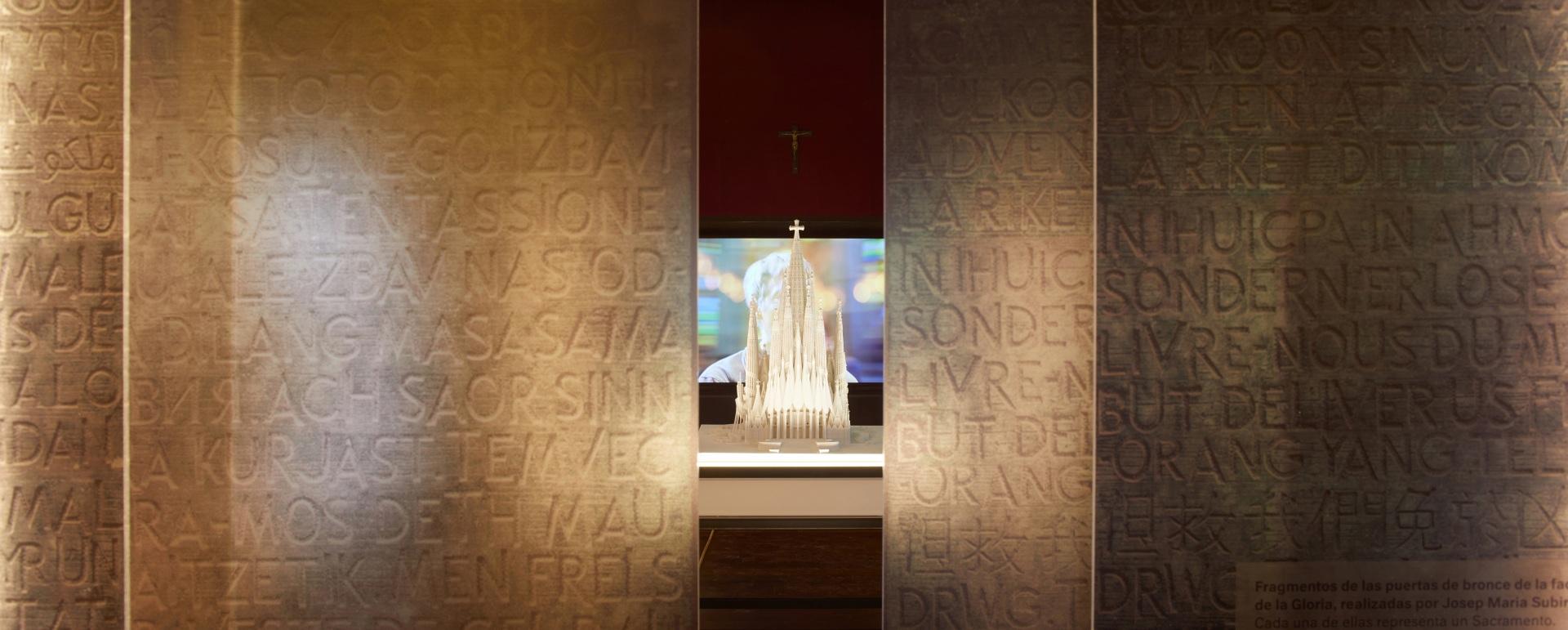 Exposición Gaudí Sagrada Familia. Puertas abiertas con maqueta del edificio y proyección audiovisual de fondo.