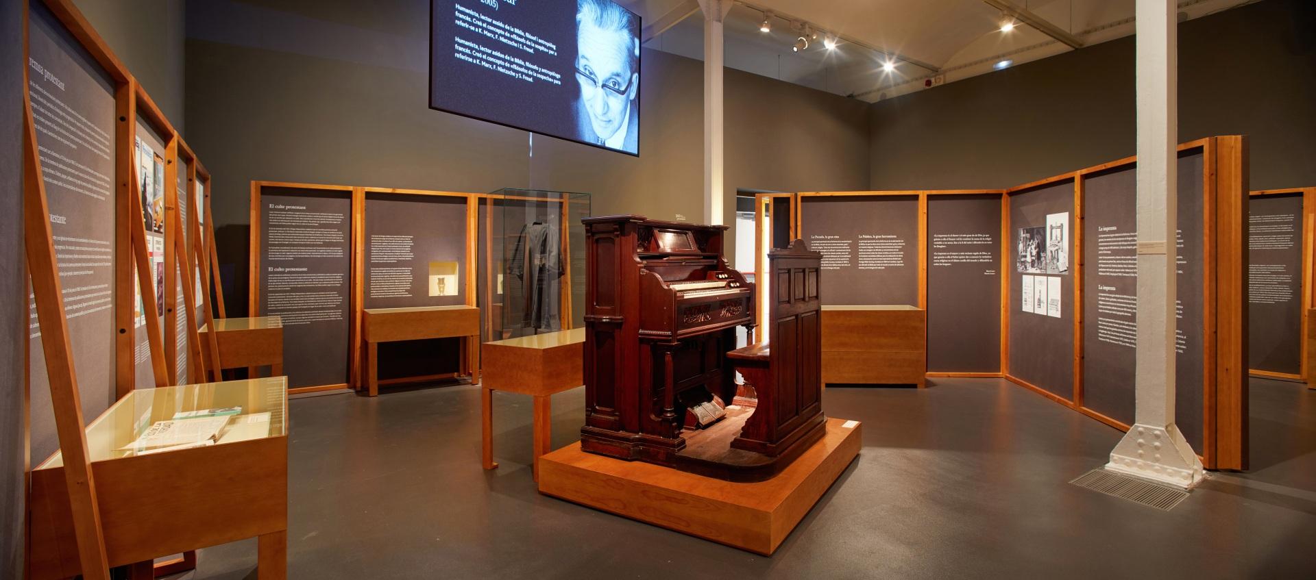 Exposición protestantes Caixaforum. Armónium antiguo de madera, proyección audiovisual y toga. De fondo, paneles explicativos y vitrinas.