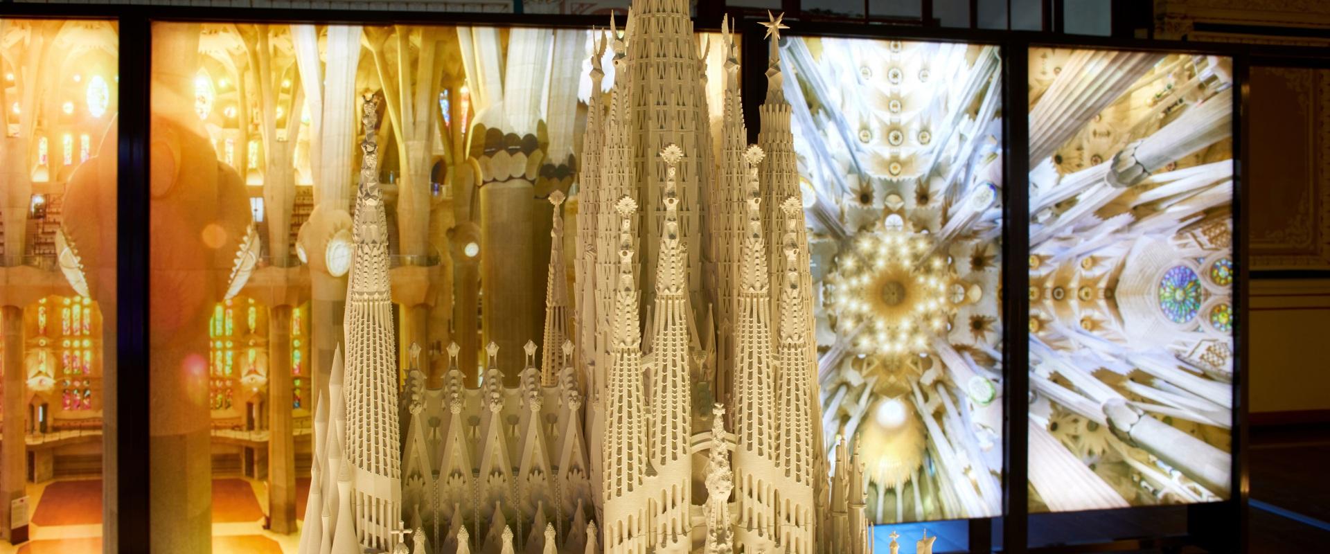 Exposición Gaudí Sagrada Familia. Maqueta iluminada con imágenes del interior del edificio en tonos naranjas.