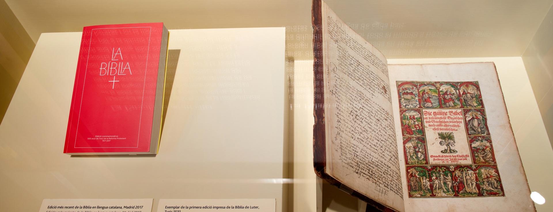 Exposición protestantes Caixaforum. Vitrina con una primera edición de la Biblia protestante y una última edición de la Biblia protestante.