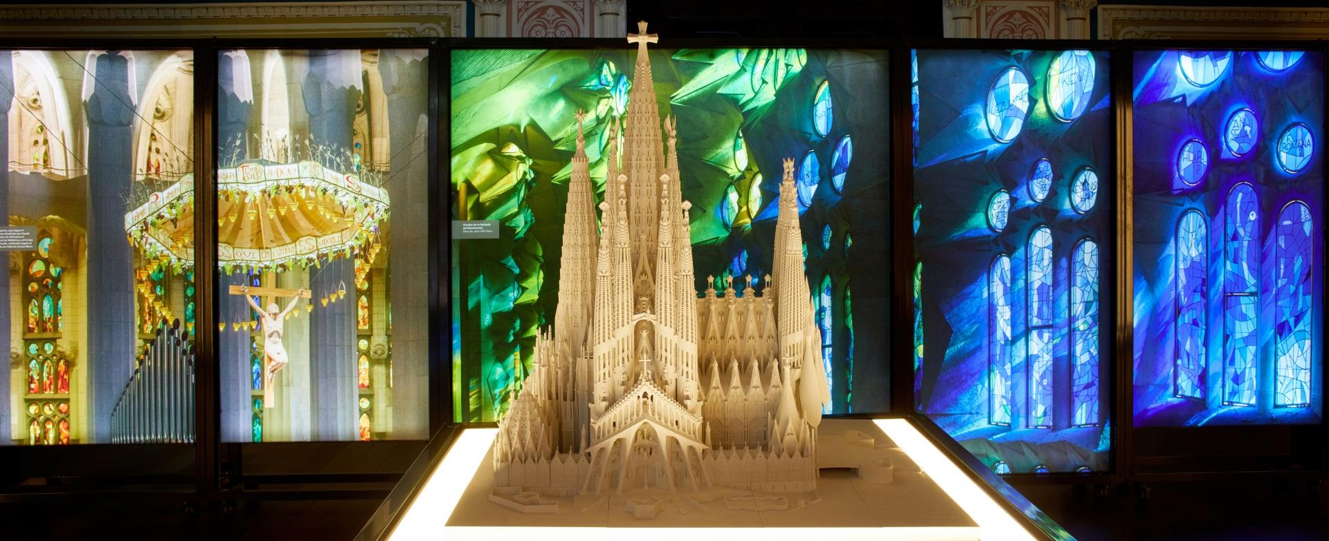 Exposición Gaudí Sagrada Familia. Maqueta iluminada. De fondo, cajas iluminadas con imágenes de vidrieras de color azul y verde y escultura de Jesucristo bajo baldaquino.