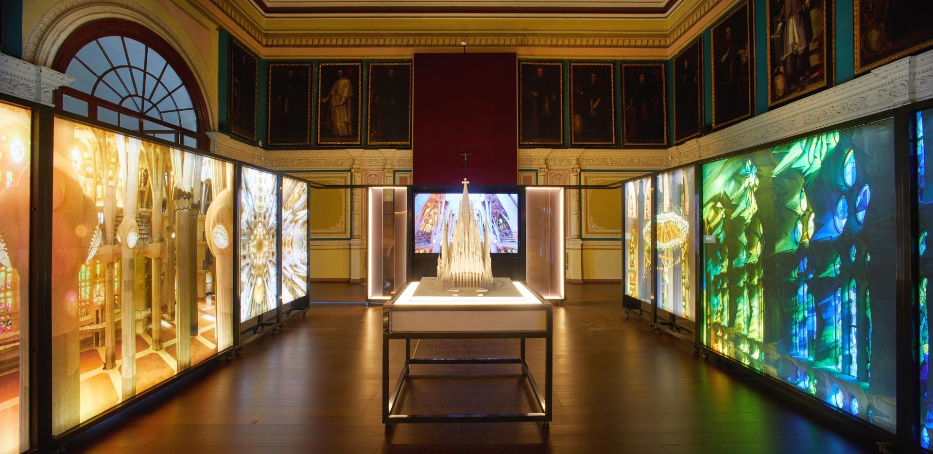 Exposición Gaudí Sagrada Familia. Maqueta iluminada rodeada de imágenes de vidrieras del interior en colores verde, azul y naranja. Con proyección de fondo, en una sala antigua con retratos de cardenales.
