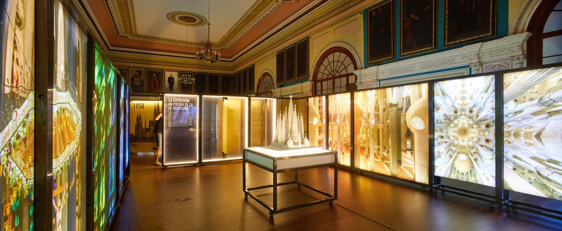 Exposición Gaudí Sagrada Familia. Maqueta iluminada rodeada de imágenes de vidrieras del interior en colores verde, azul y naranja. En una sala antigua con retratos de cardenales.