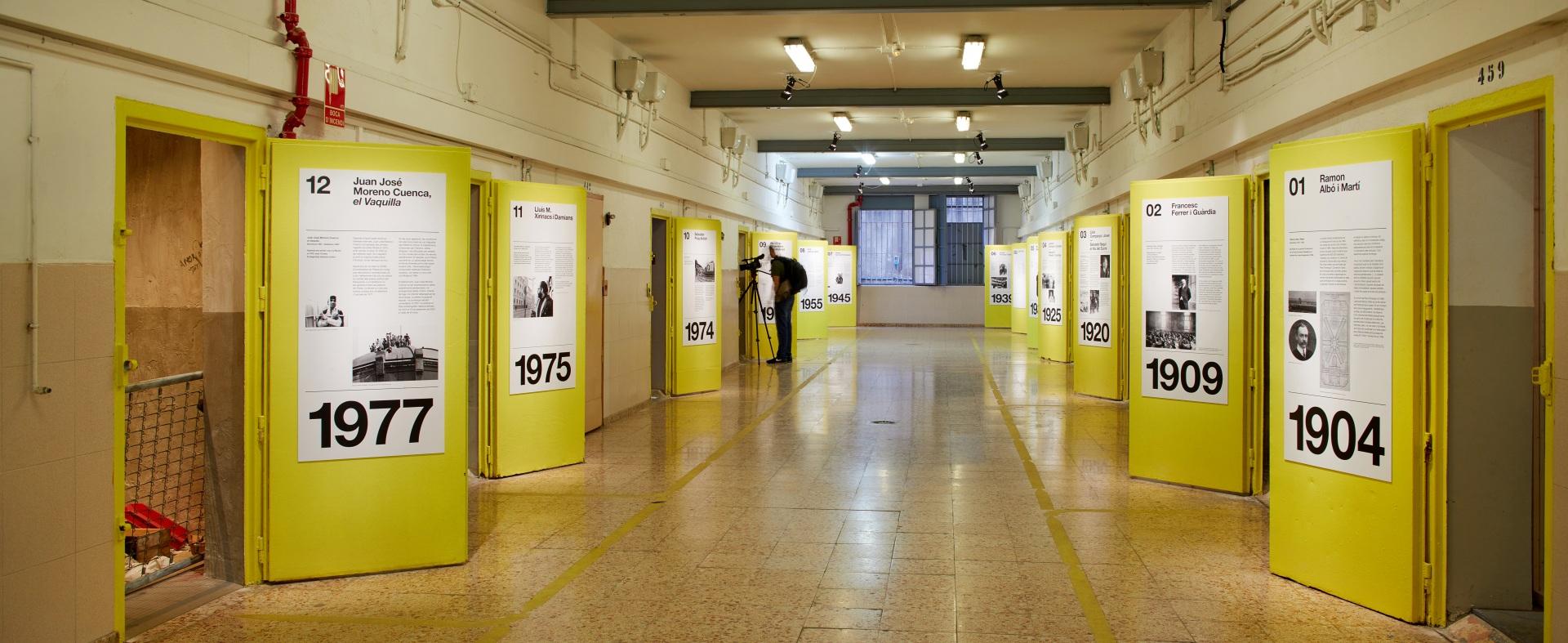 Visita museizada a la Presó Model. Galería 5, rejas de acceso y puertas amarillas. Fotógrafo al fondo.