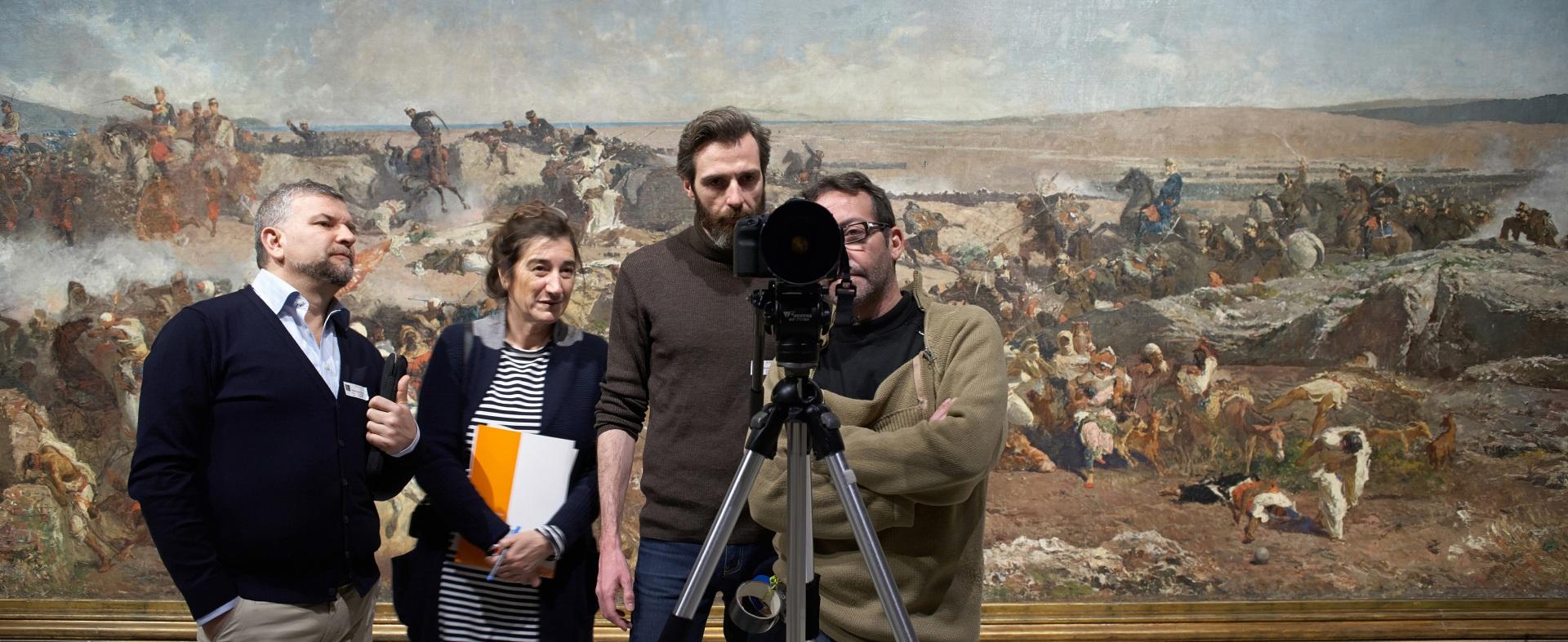 Making of de documental. Productor, director, ayudante de dirección y director de fotografía detrás de la cámara delante de cuadro de paisaje en guerra en el Museu Nacional d\'Art de Catalunya.