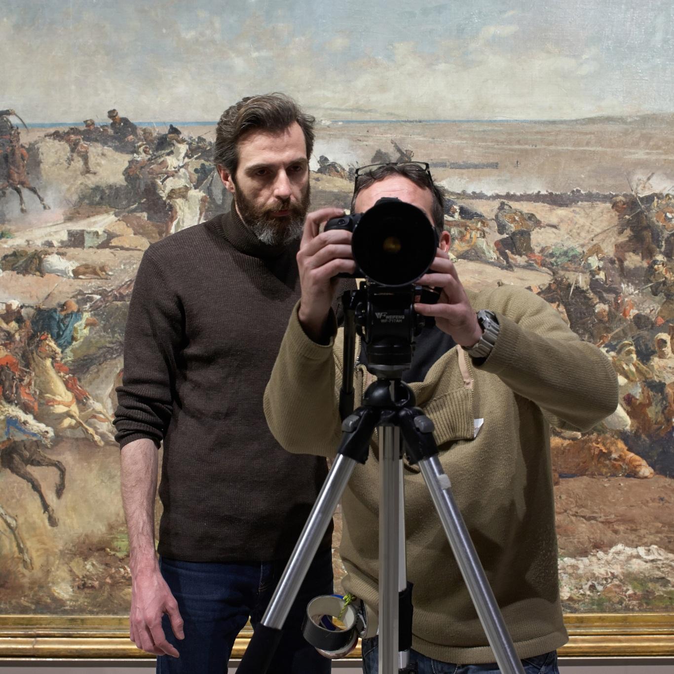 Making of de documental. Director y director de fotografía delante de cuadro de paisaje en guerra en el Museu Nacional d\'Art de Catalunya.