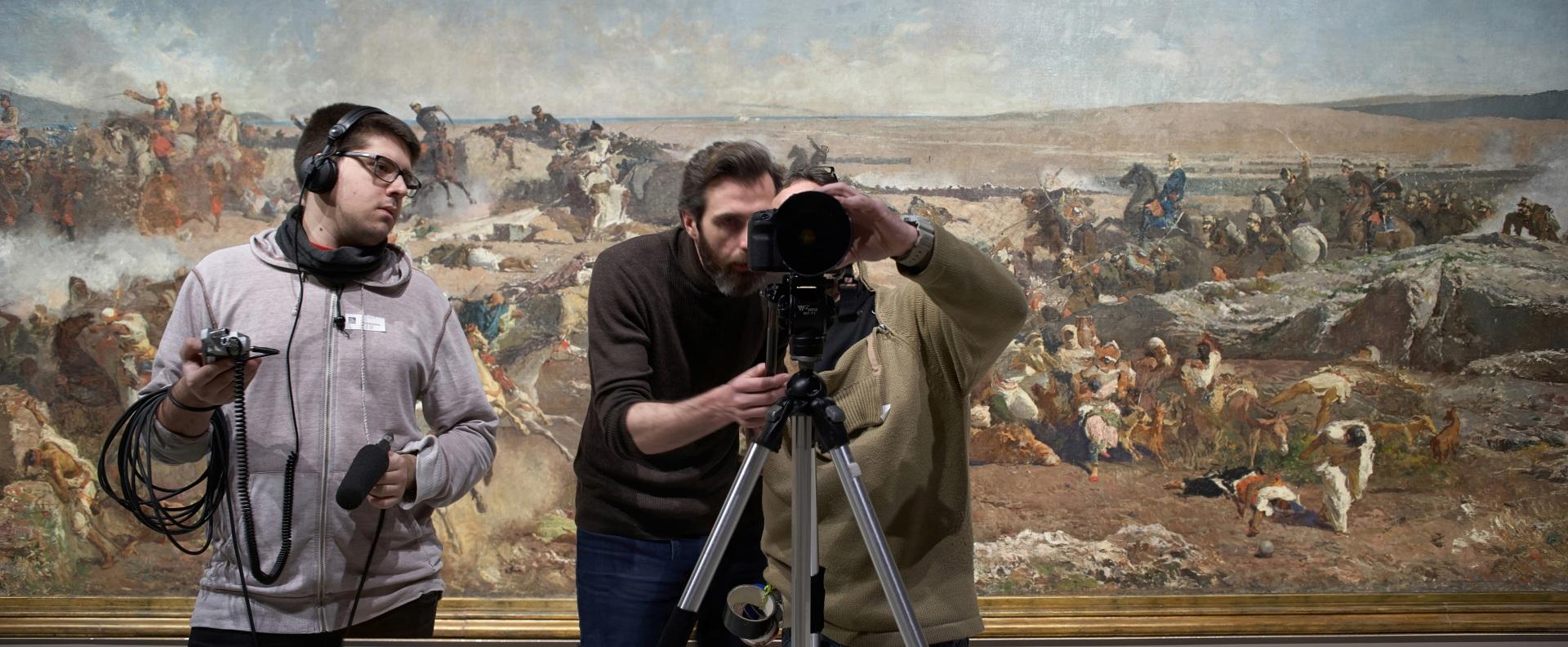 Making of de documental. Técnico de sonido, director y director de fotografía delante de cuadro de paisaje en guerra en el Museu Nacional d\'Art de Catalunya.