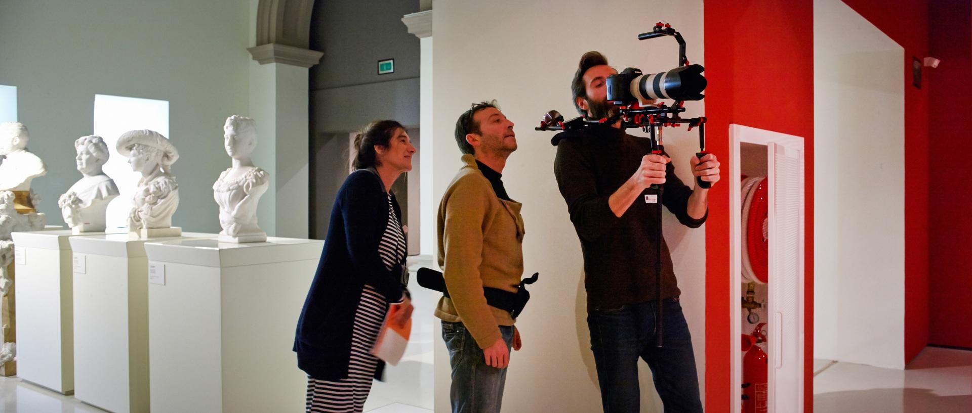 Making of de documental. Esculturas blancas, ayudante de dirección, director de fotografía y director con la cámara grabando en el Museu Nacional d\'Art de Catalunya.