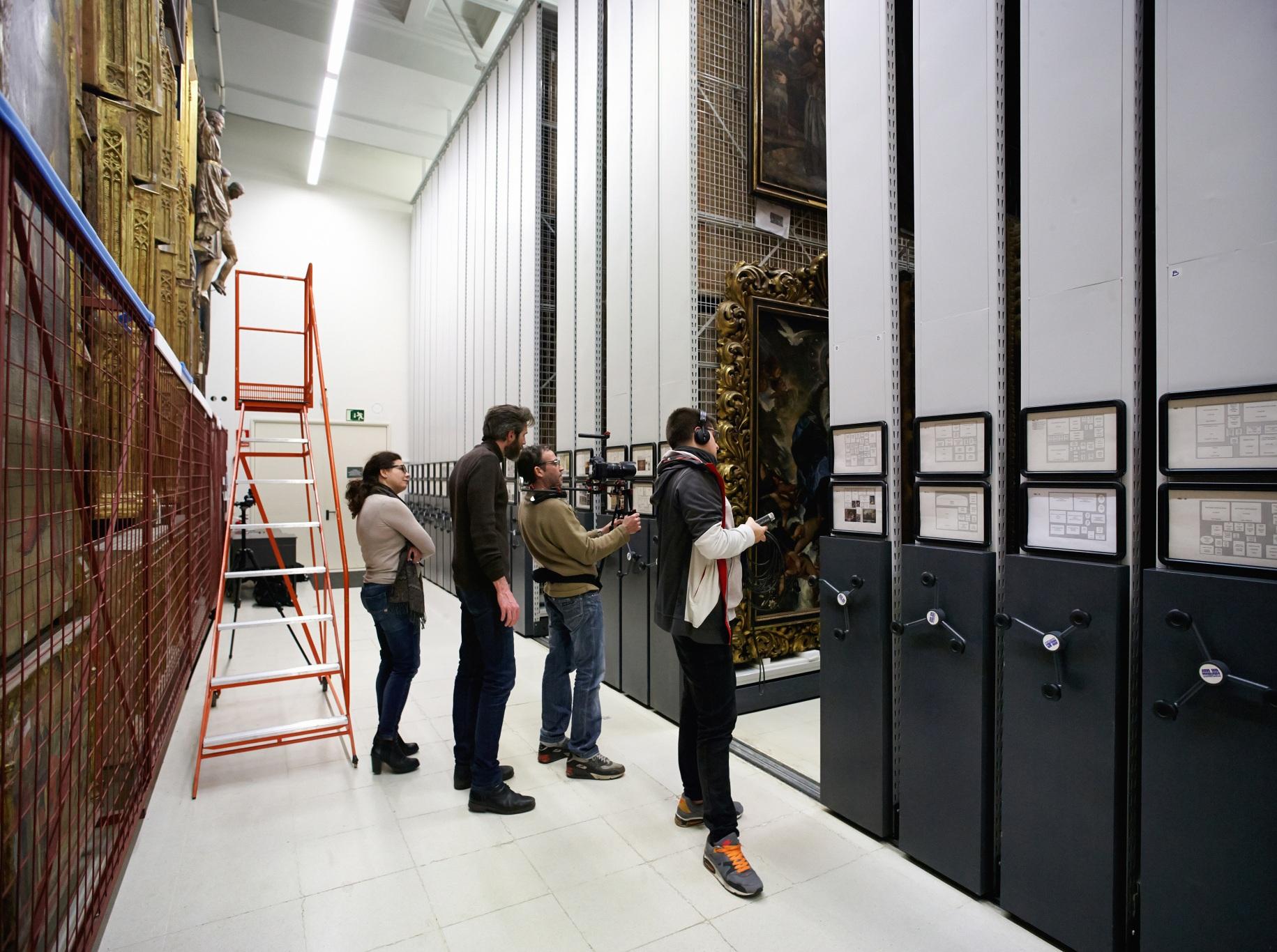 Making of de documental. Director, director de fotografía y técnicos grabando en los archivos de obras de arte del Museu Nacional d\'Art de Catalunya.