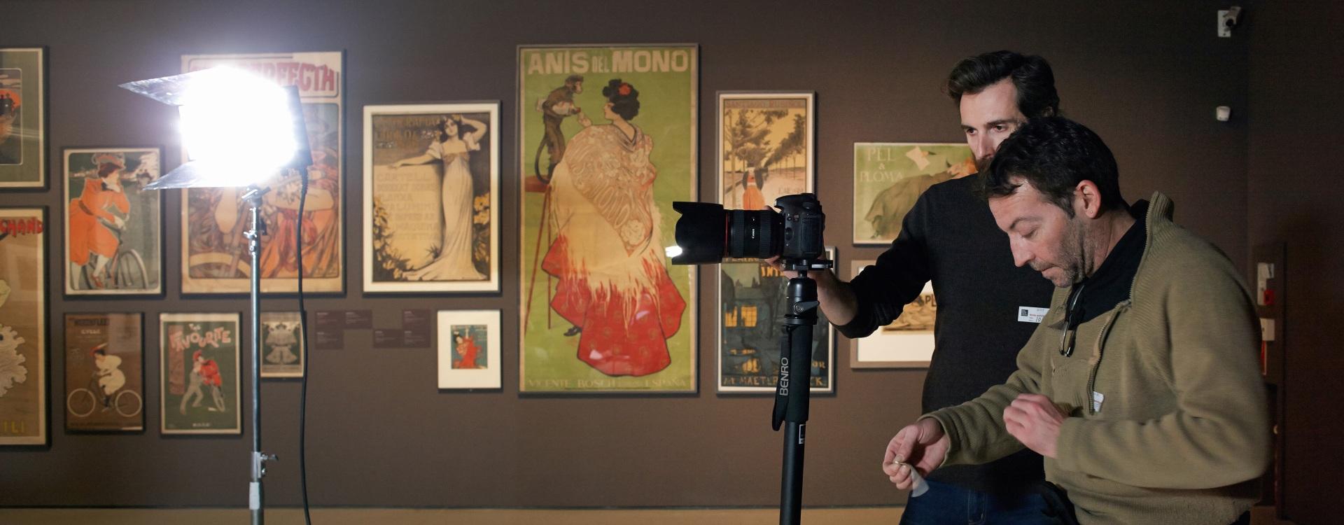 Making of de documental. Director y director de fotografía grabando en el Museu Nacional d\'Art de Catalunya. Foco de luz, carteles y pinturas.