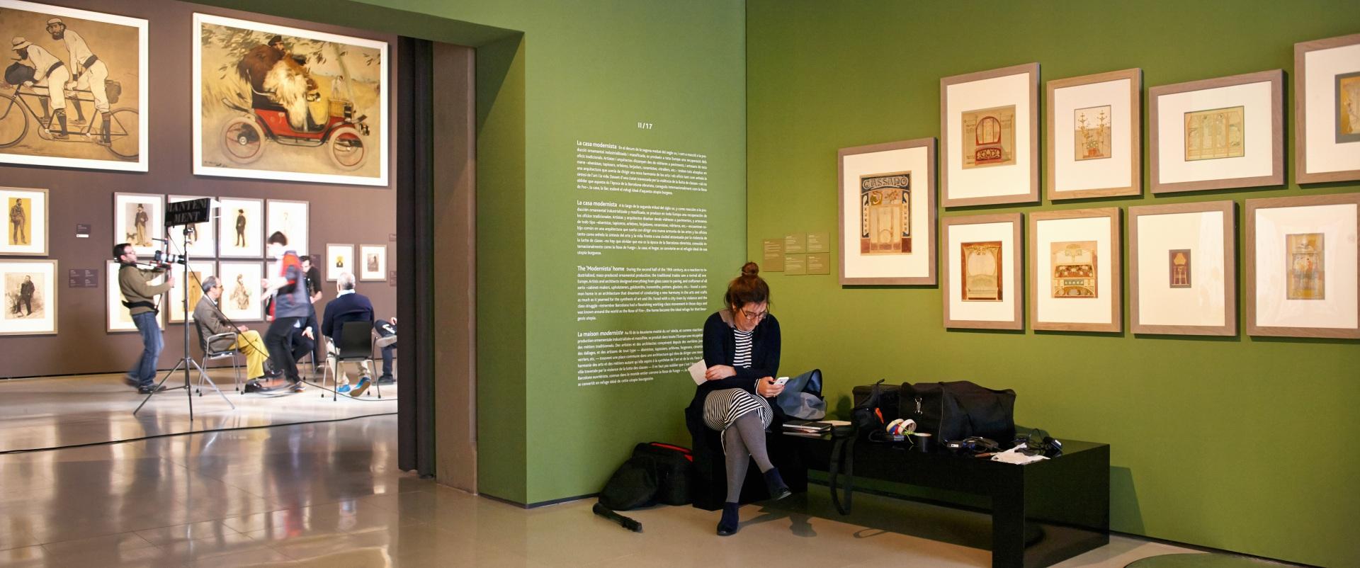Making of de documental. Ayudante de dirección sentada en una de las salas del Museu Nacional d\'Art de Catalunya. Dibujos de muebles sobre una pared verde. De fondo, comisario, productor y técnicos en torno a cuadros de Ramon Casas y otros artistas de Els Quatre Gats.