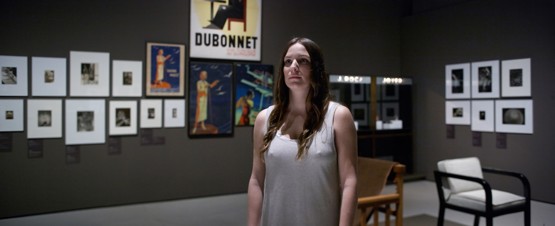 Making of de documental. La noia, una modelo que deambula por el Museu Nacional d\'Art de Catalunya. De fondo carteles y pinturas.
