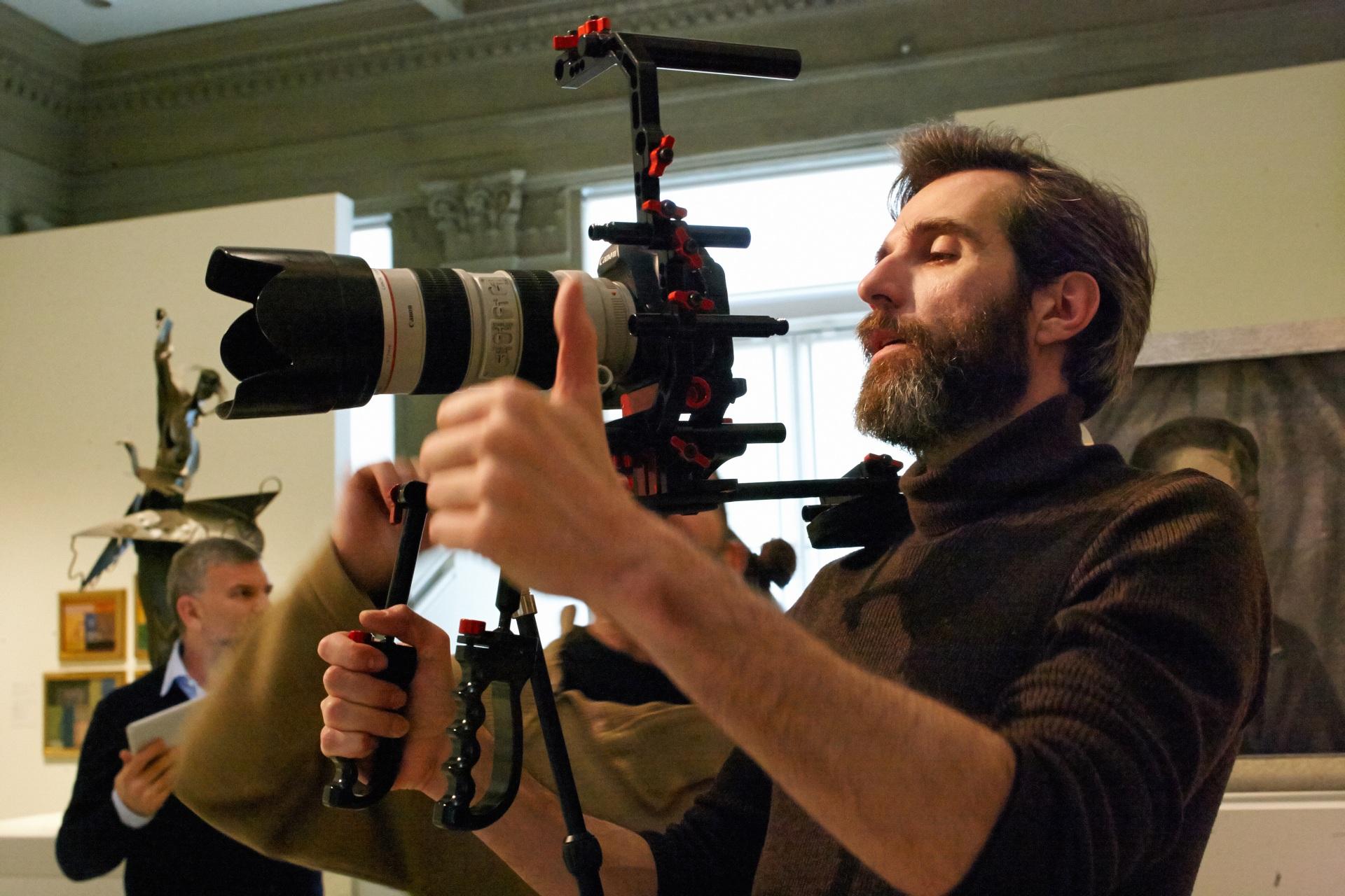 Making of de documental. Director sujetando la cámara. De fondo, productor y escultura en una sala del Museu Nacional d\'Art de Catalunya.