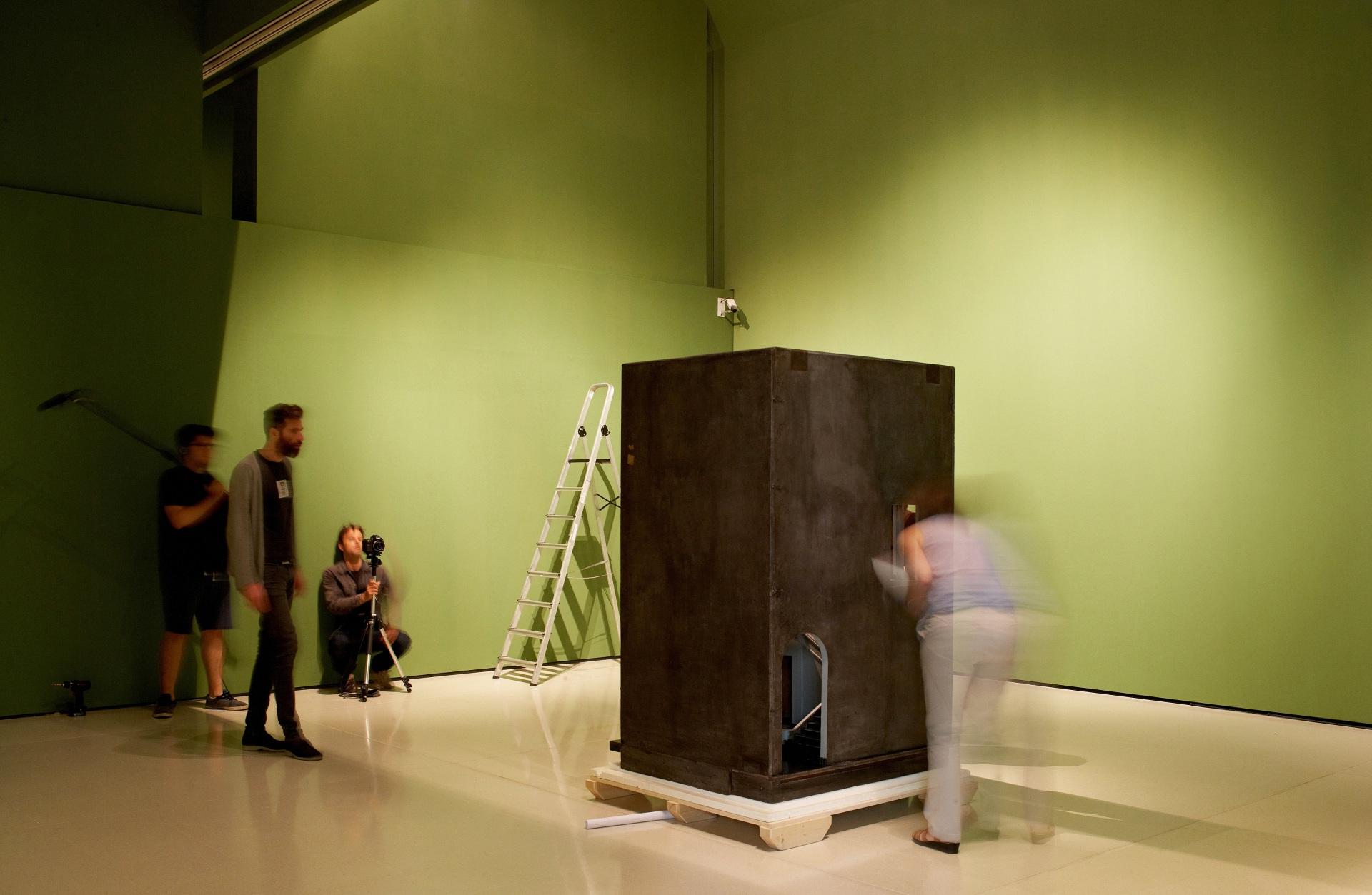 Making of de documental. Director y técnicos en una sala del Museu Nacional d\'Art de Catalunya. Obra de arte en forma de caja negra. De fondo, escalera de mano sobre fondo verde.