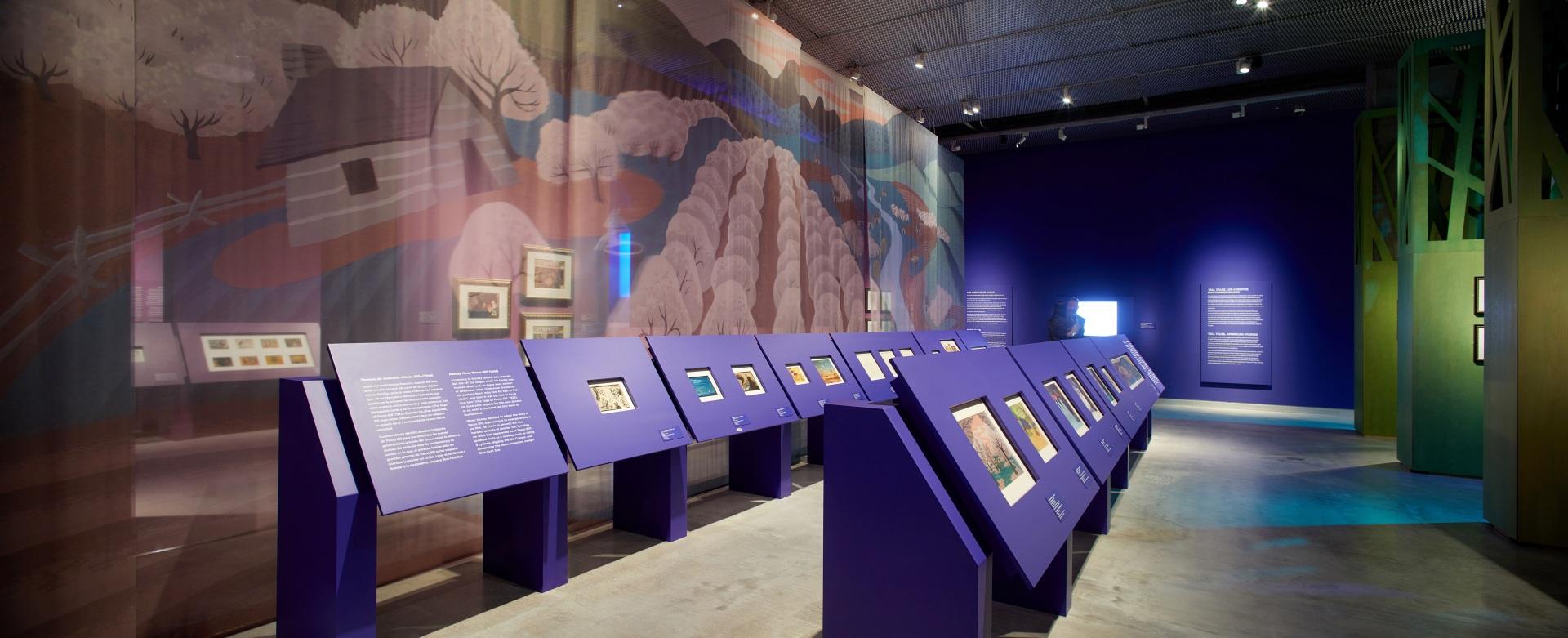 Exposición sobre Walt Disney. Mesas de dibujo color morado. Paisaje de colores de fondo.