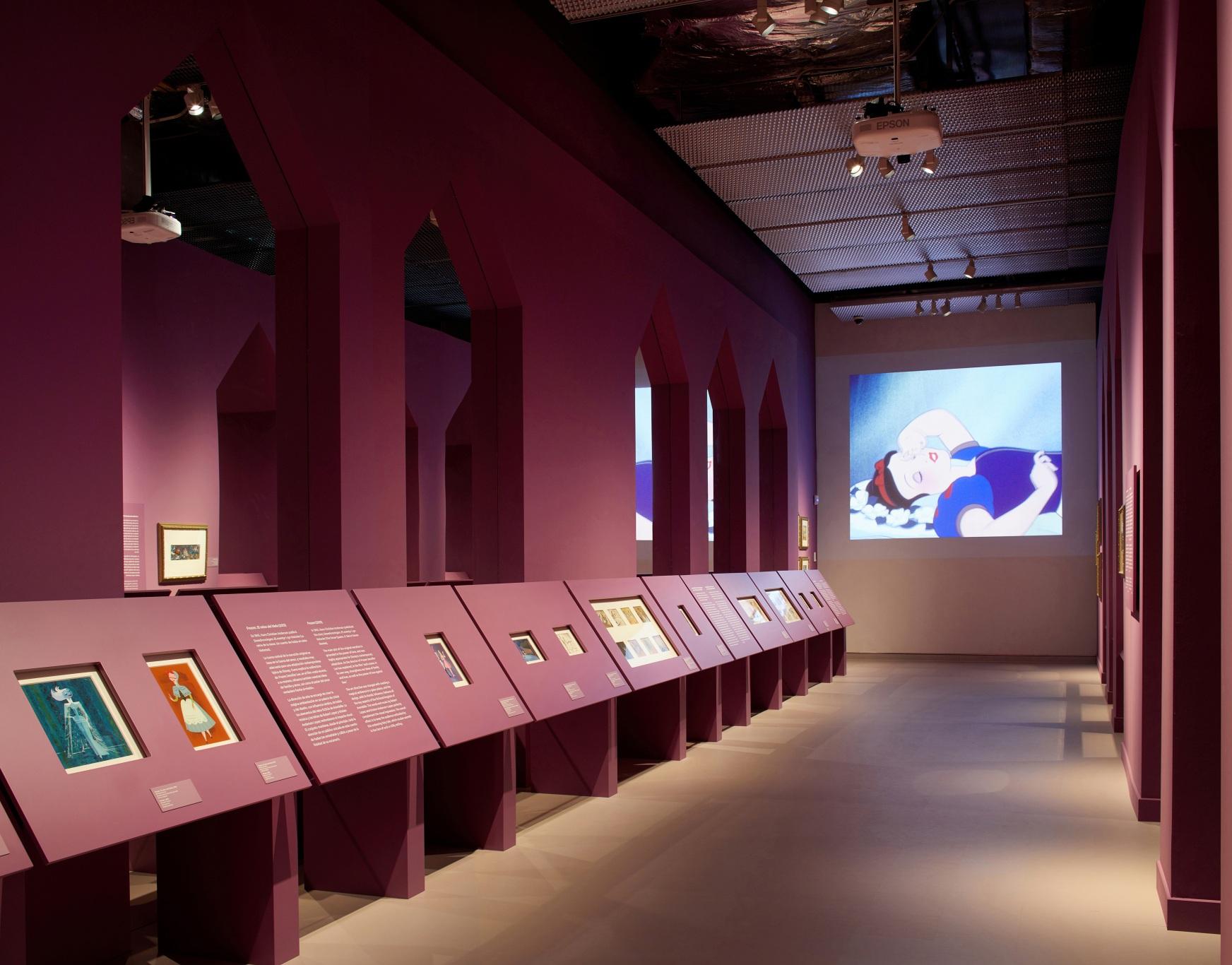 Exposición sobre Walt Disney. Castillo encantado de las princesas color magenta. Imagen de Blancanieves de fondo.