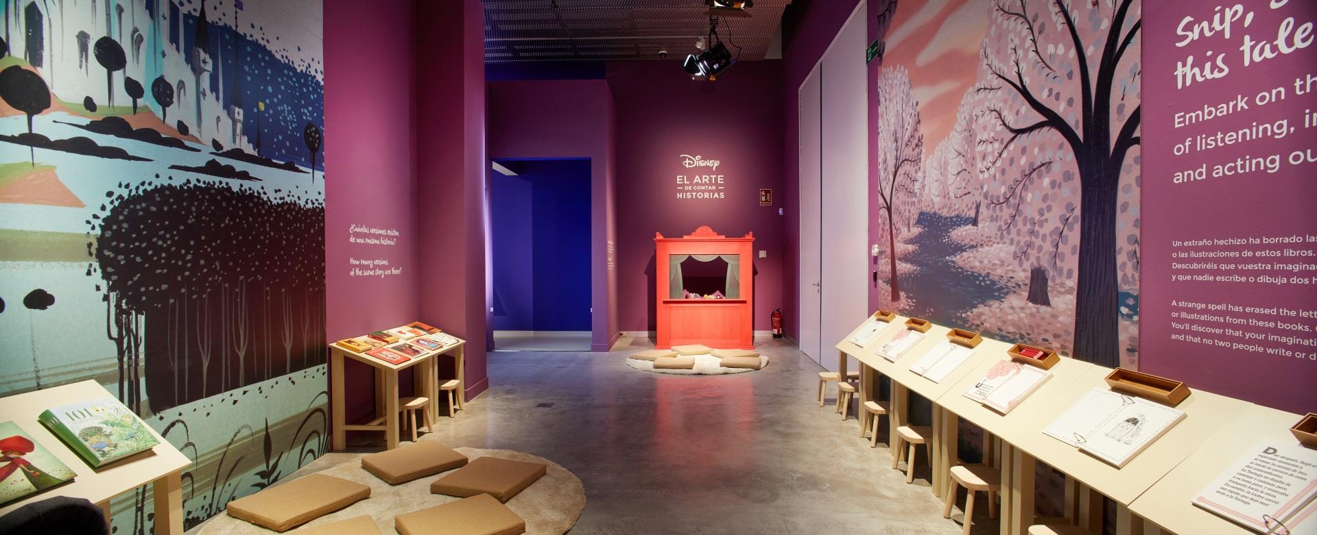 Exposición sobre Walt Disney. Espacio infantil con paisajes de colores de fondo. Mesas de dibujo para niños. Teatro de marionetas.
